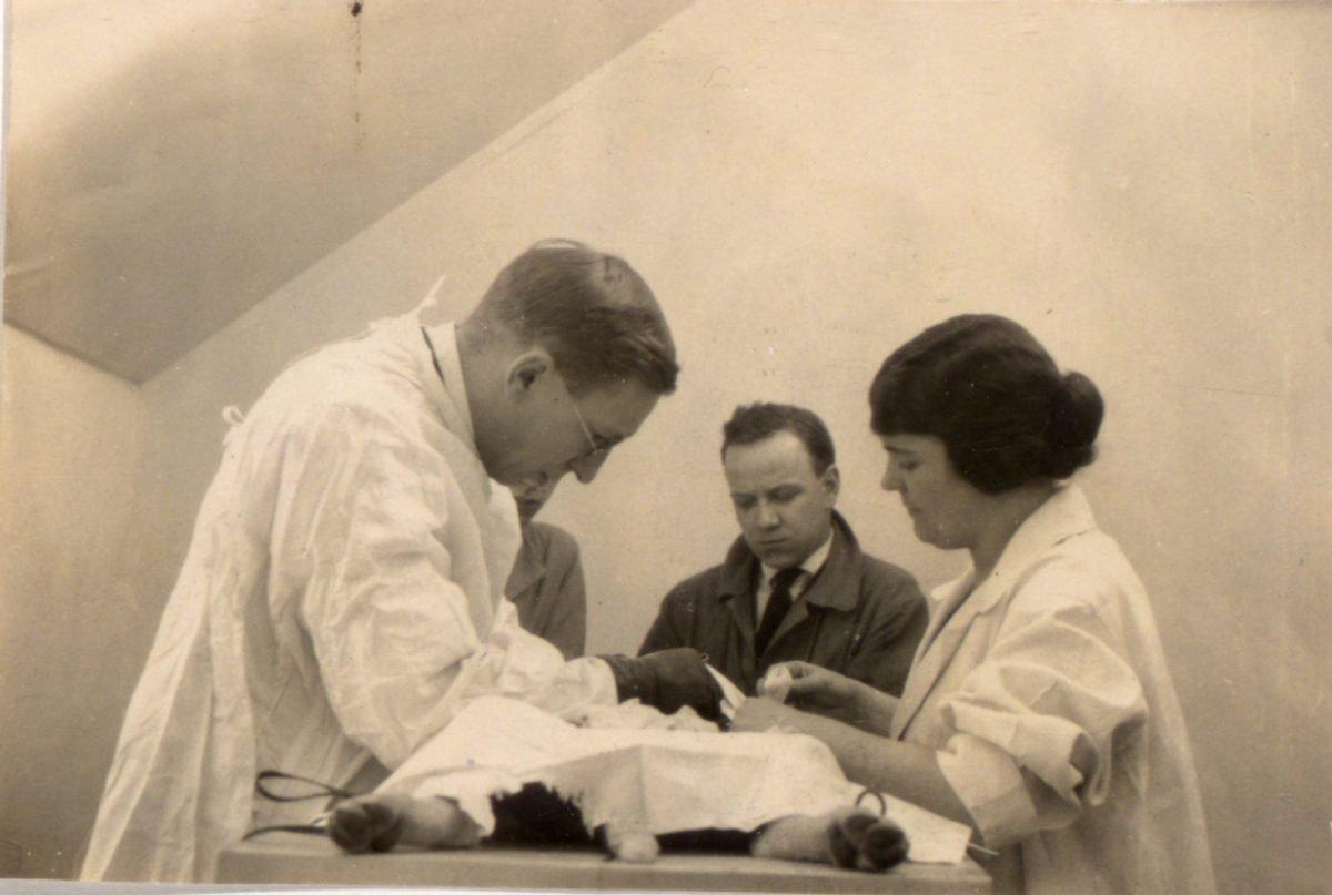 Fotografía original en blanco y negro que muestra a Banting, asistido por Sadie Gairns, realizando una cirugía en un perro. Hombre no identificado en el fondo. 1922. 4 de agosto. 1921 - El perro 408 recibió la inyección de «Isletin» por primera vez. Los científicos también experimentan con conejos.