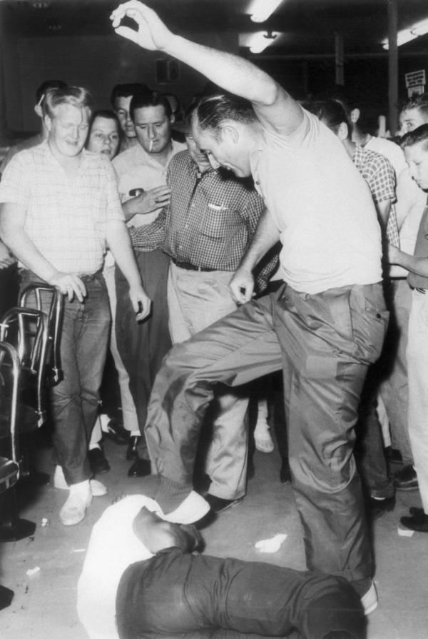 Benny Oliver, ex policía de Jackson, Mississippi, patea con saña a Memphis Norman, un estudiante afroamericano de la cercana ciudad de Wiggins que había estado esperando junto con otros dos estudiantes a que le sirvieran en un mostrador de almuerzo segregado. El rumor de posibles represalias de derechos civiles en la ciudad motivó que los espectadores aclamaran la paliza. El 28 de mayo de 1963.