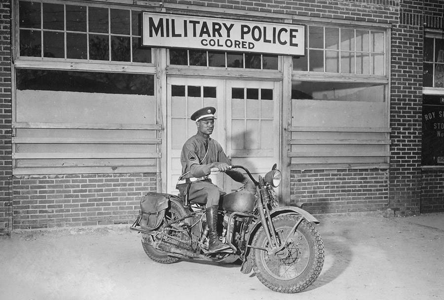 Un policía militar afroamericano en su motocicleta frente a la entrada de la policía militar de color. Columbus, Georgia. 1942.