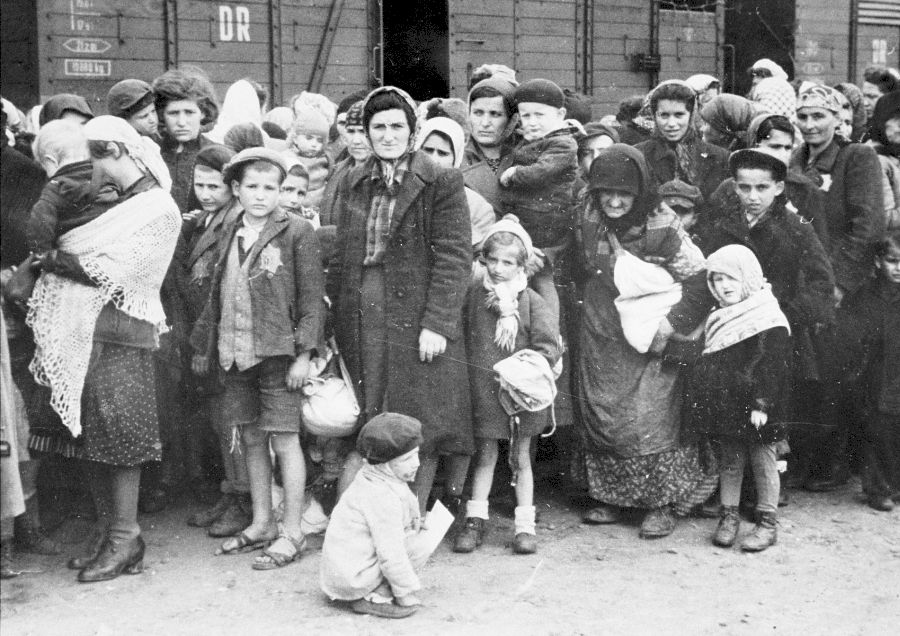Las mujeres y niños judíos de la Rusia subcarpática esperan ser seleccionados en la rampa de Auschwitz-Birkenau. Entre los que aparecen en la foto están Irina Berkovits (37 años) y su hijo Adalbert (5 años), ambos fallecidos. También están Hajnal Klein y sus cuatro hijas Lili (18 años), Herczi (15 años), Renee (12 años) e Iren (7 años). Hajnal, Renee e Iren fueron asesinados al llegar. Lili y Herczi sobrevivieron.