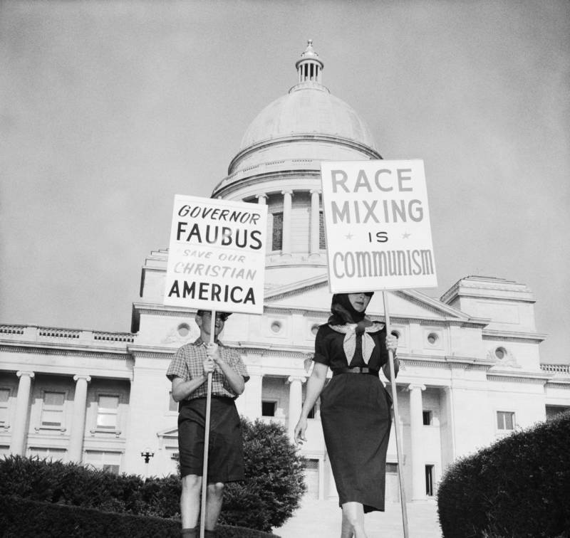 Una mujer y un niño, que se negaron a identificarse, marchan frente al Capitolio de Arkansas en Little Rock en protesta por la integración programada de las escuelas secundarias de esta ciudad. 1957.
