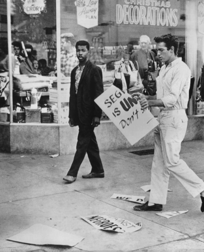 Un joven blanco rompe el cartel de un manifestante negro que estaba haciendo piquete en delante de una tienda para protestar por sus políticas de segregación. Tallahassee, Florida, 1960.