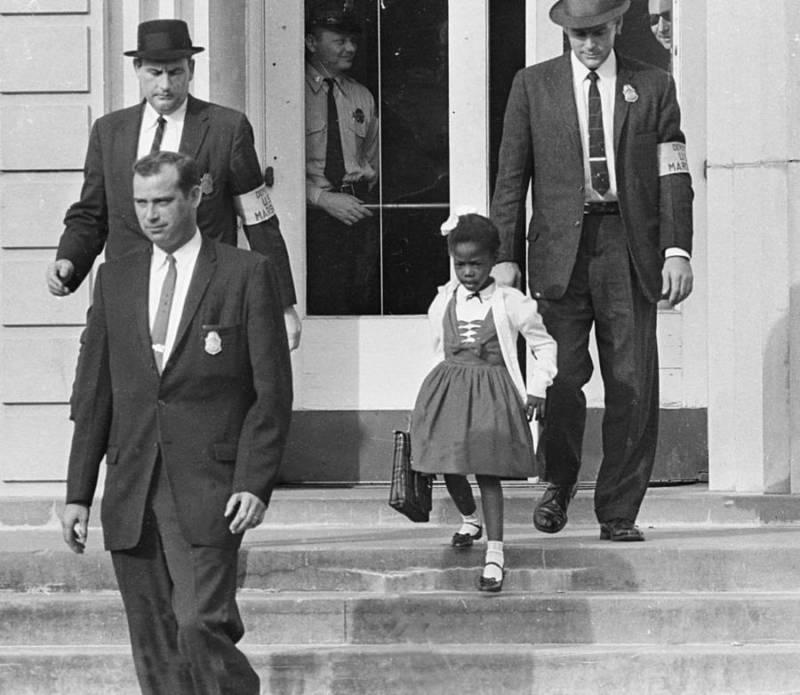 Ruby Bridges de seis años es escoltada de la escuela por los US Marshals. Bridges fue la primera niña afroamericana en desegregar la Escuela Primaria William Frantz de Luisiana, totalmente blanca, durante la crisis de desegregación escolar de Nueva Orleans en 1960.