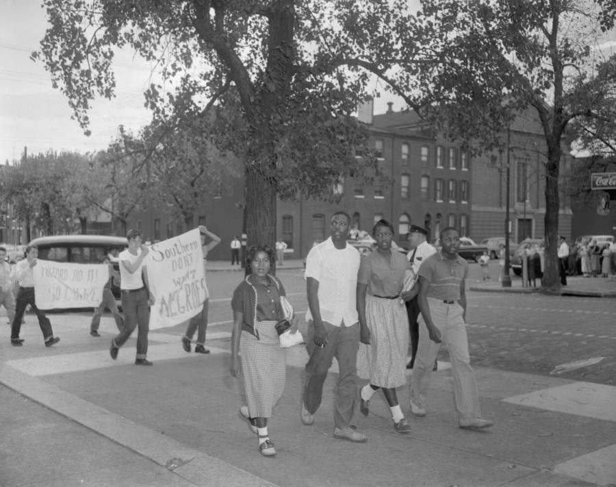 """Los estudiantes afroamericanos llegan a Baltimore, la recién integrada Southern High School de Maryland mientras los estudiantes blancos caminan detrás con un letrero que dice """"Los sureños no quieren negros"""". 1954."""