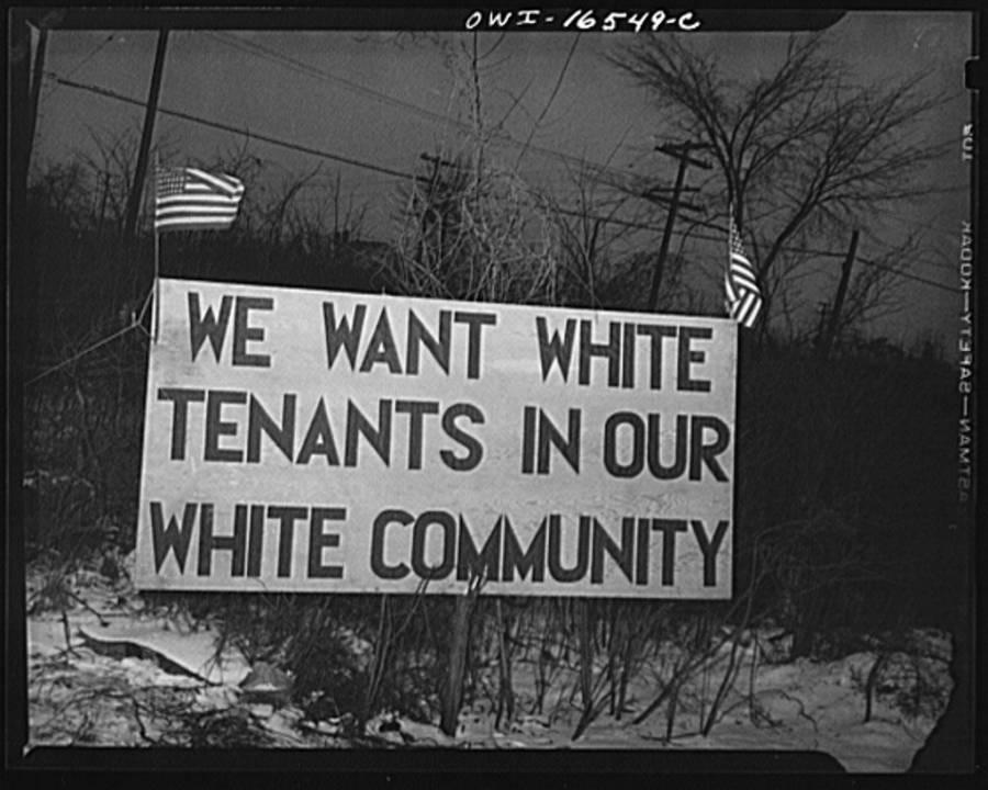 Un cartel justo enfrente de las viviendas de Sojourner Truth, un nuevo proyecto federal de viviendas en Detroit, Michigan. El disturbio fue causado por los reiterados intentos de los vecinos blancos, con la finalidad de evitar que los inquilinos afroamericanos se mudaran. 1942.